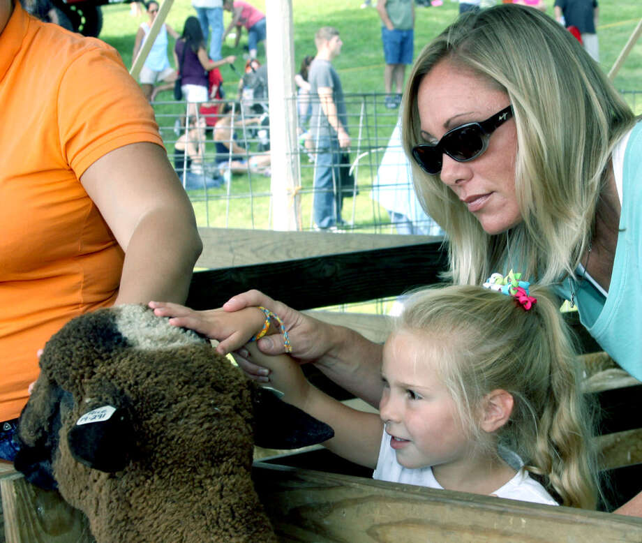 Samantha Morits, 4, of New Fairfield and her mom, Courtney, pay a visit to a sheep at the Bridgewater Country Fair, Aug. 17, 2013. Photo: Walter Kidd