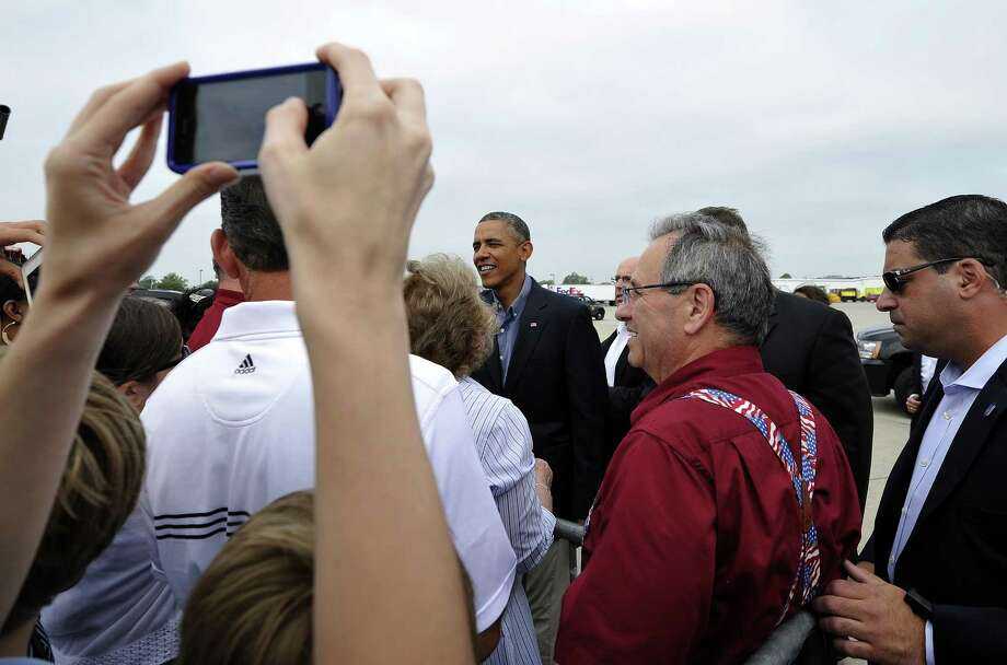 US President Barack Obama (C) greets a crowd of people upon arriving at the Buffalo Niagara International Airport on August 22, 2013 in Buffalo, New York. Obama is on a two-day bus tour through New York and Pennsylvania to discuss his plan to make college more affordable, tackle rising costs, and improve value for students and their families. AFP Photo/Jewel SamadJEWEL SAMAD/AFP/Getty Images Photo: JEWEL SAMAD, Getty / AFP