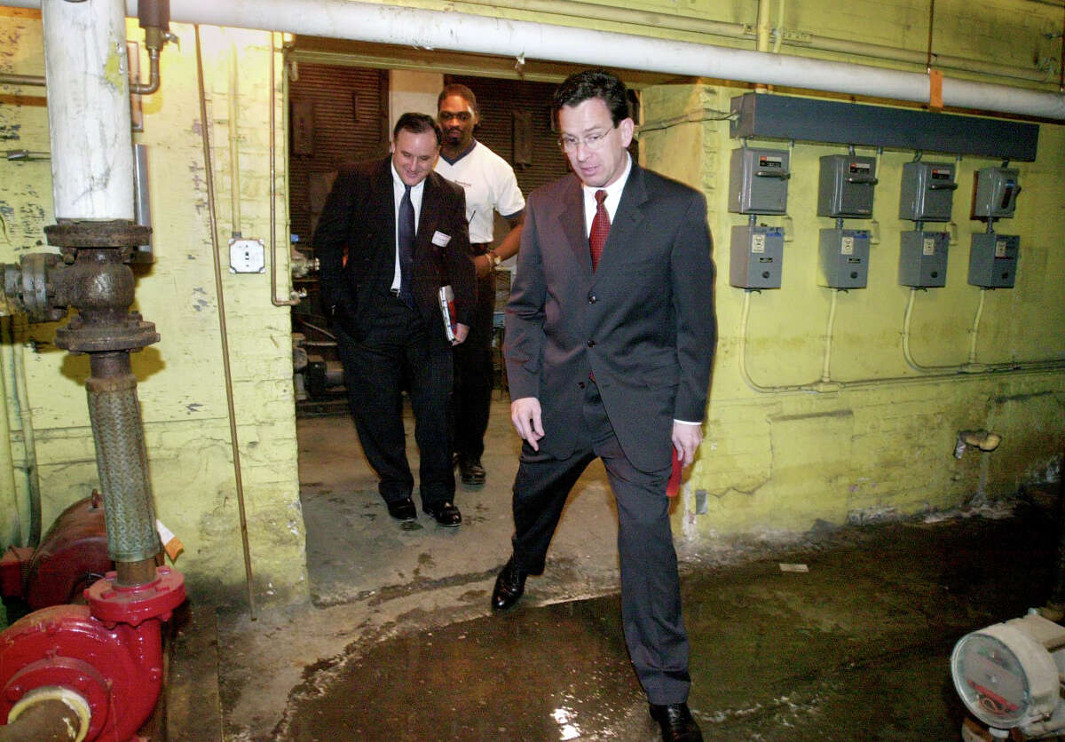 Stamford Mayor Dannel Malloy steps over a puddle of water in the boiler room of Rogers Elementary School during a tour of the Stamford, Conn. facilities in 2001. In the back are Al Barbarotta of the Stamford Public Schools Facilities Management, far left, and Robert Malcolm, head custodian.