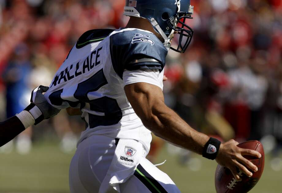 Seahawks quarterback Seneca Wallace is grabbed from behind by Manny Lawson in the fourth quarter of the 49ers home opener in 2009. Photo: Brant Ward, The Chronicle