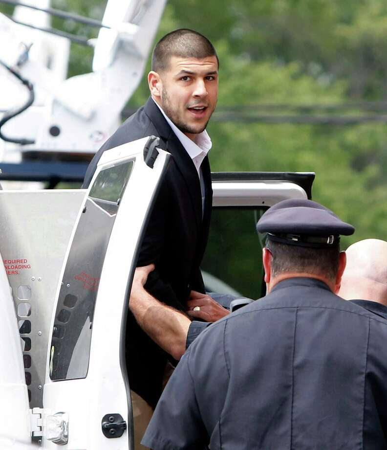 Former New England Patriots NFL football tight end Aaron Hernandez is led out of a van as he arrives for his probable cause hearing at Attleboro District Court, on Wednesday, July 24, 2013, in Attleboro, Mass. Hernandez has pleaded not guilty to murder in the death of Odin Lloyd. A judge rescheduled the probable cause hearing for Aug. 22, after considering defense objections to a delay. (AP Photo/Bizuayehu Tesfaye) Photo: Bizuayehu Tesfaye, Associated Press / FR30253 AP