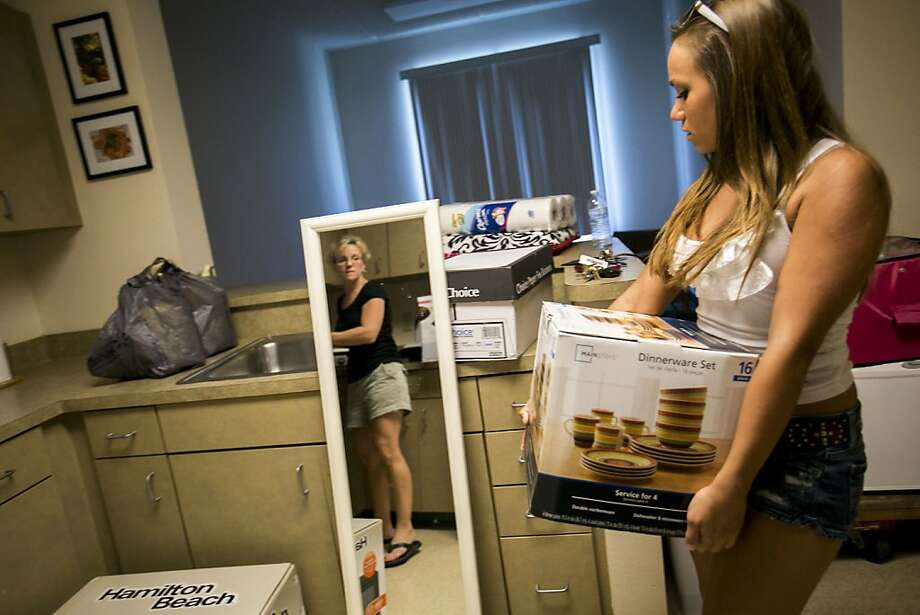 Matching china is a priority in today's freshman dorms: Jessica Tardibuono carries a box of dishes into the kitchen of her dorm 