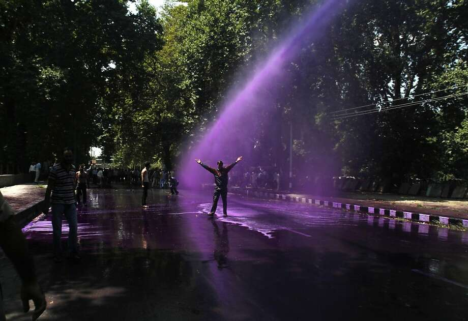 The purple hose of Kashmir: Police douse a Kashmiri government worker with colored water during a protest in 