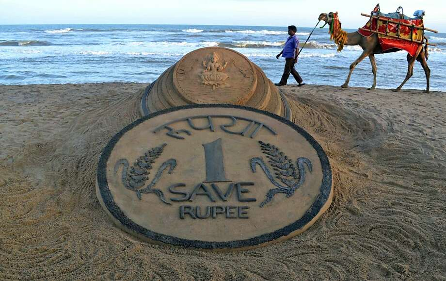 Making rupee: Having plunged to new lows against the dollar almost daily, the rupee now has even Puri sand sculptors feeling sorry for it. Asia's worst performing currency shows no sign of stemming the free fall. Photo: Biswaranjan Rout, Associated Press