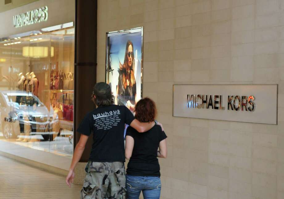 Shoppers walk by Michael Kors at the Danbury Fair in Danbury, Conn. on Thursday, Aug. 22, 2013.  The mall is becoming a destination shopping area, seeing an increase in out-of-state shoppers with the upscaling of its tenants.  Some of the more upscale shopping areas in and around the mall include Brooks Brothers, Michael Kors, Microsoft and Jos. A. Bank. Photo: Tyler Sizemore / The News-Times