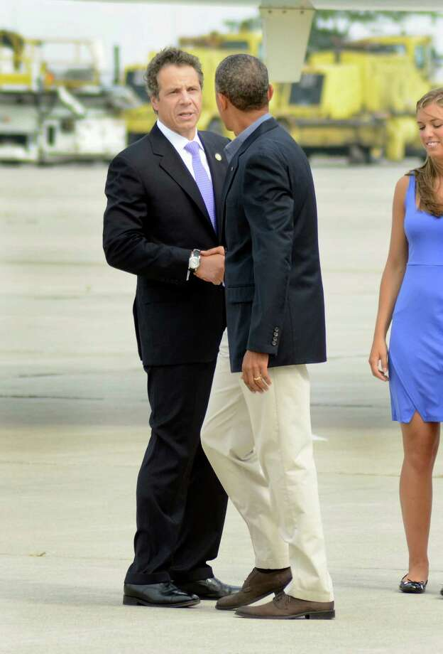 New York State Gov. Andrew Cuomo shakes hands with President Barack Obama after Obama arrived at Buffalo Niagara International Airport in Buffalo, N.Y.,, Thursday, August 22, 2013. (AP photos/Heather Ainsworth) ORG XMIT: NYHA204 Photo: Heather Ainsworth, AP / FR120665 AP