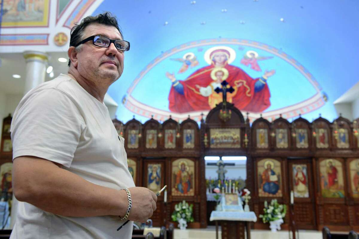 Dhimitri Cika, a professional icon painter, stands in front of his painting of the birth of Christ above the alter at St. Dimitrie Orthodox Church in Easton. Cika has undertaken the job of painting the icons for all four walls of the church which moved from Bridgeport to Easton a few years ago.