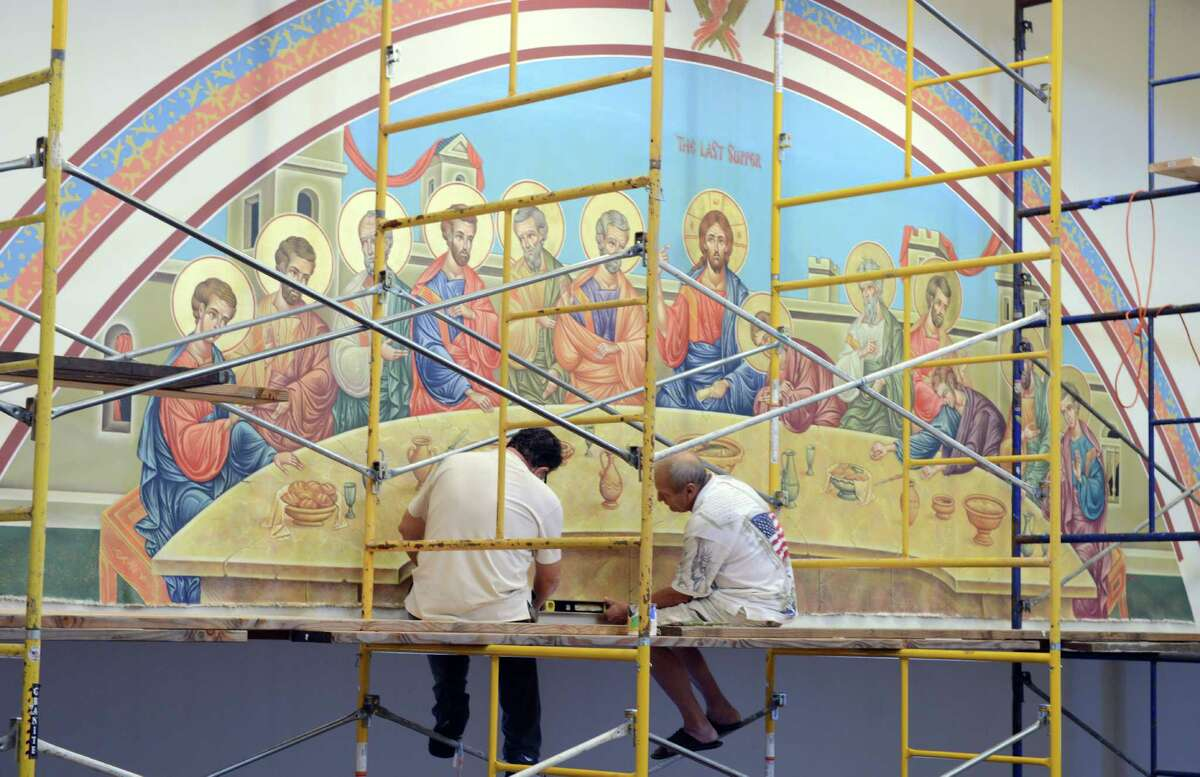 Dhimitri Cika, a professional icon painter, left, and parishioner Joseph Pusztay take measurements as they prepare to hang the border around Cika's canvas painting of the last supper on the wall of St. Dimitrie Orthodox Church in Easton. It will take around three years to complete the paintings for the church which moved from Bridgeport to Easton recently.