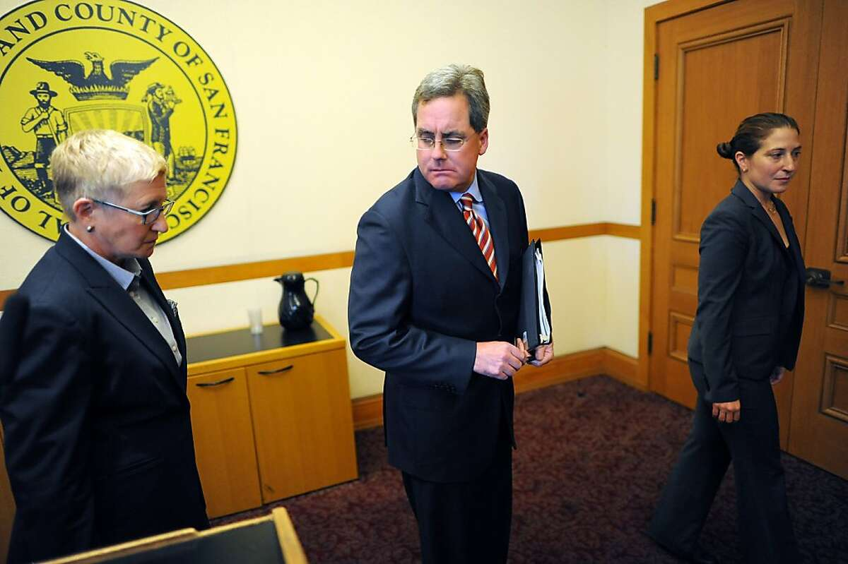 Flanked by Chief Deputy City Attorney Theresa Stewart, left and Sara Eisenberg, right, City Attorney Dennis Herrera leaves the room after reporting during a press conference at City Hall that he has filed dual legal challenges to the possible termination of City College of San Francisco's accreditation, in San Francisco, California on Thursday, August 22, 2013.