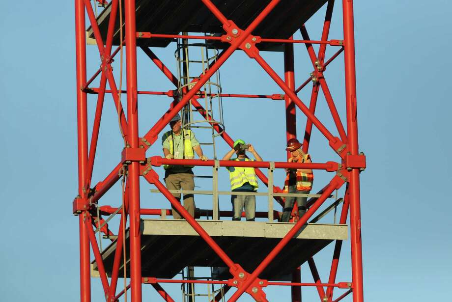 "Workers watch from a crane on the site of the Capitol Hill light rail station in Seattle as Macklemore and Ryan Lewis prepare to perform for a video shoot on Wednesday, July 24, 2013, on the roof of the Capitol Hill Dick's Drive-In. Macklemore & Ryan Lewis were working with a crew to shoot a video for their song ""White Walls."" Thousands of people showed up for the video shoot after word of the shoot was leaked onto social media earlier in the day. The shoot was delayed because of the large crowd that showed up on Broadway Avenue. (Joshua Trujillo, seattlepi.com) Photo: JOSHUA TRUJILLO, Seattlepi.com File Photo / SEATTLEPI.COM"
