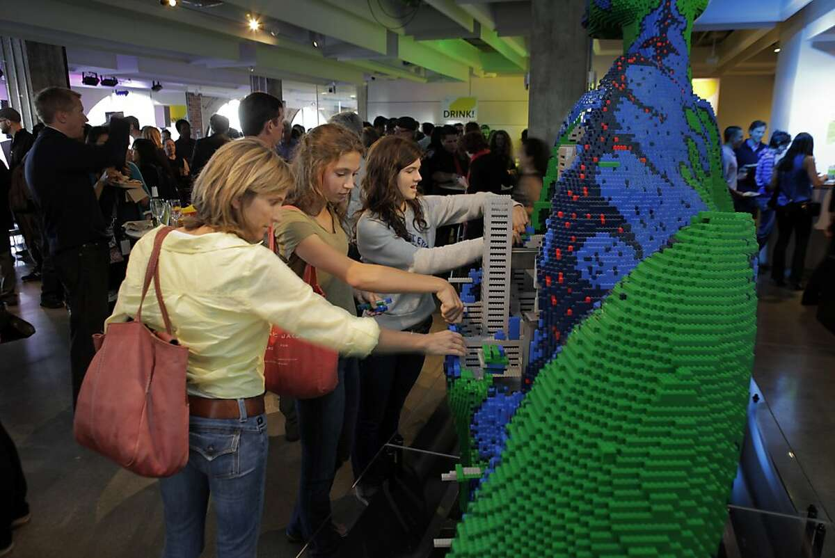 Leslie Vanoni with her two daughters Bridgette and Mia looking over the dinosaur Legoland Mega Model at Design Night at the Autodesk Gallery in San Francisco, Calif., on Thursday, August 1, 2013. The theme is music, with speakers and activities examining how technology is changing how we listen to and interact with music. Activities included self-playing drums, musical instructables, and researchers from the Center for Computer Research in Music and Acoustics at Stanford.
