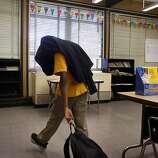Fourth grader Naias Johnson drags his belonging to the corner of the classroom, after getting in trouble, Thursday January 17, 2013,  at the100 Black Men Community  Charter School in Oakland, Calif.