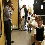 Kindergarten teacher Mr. Xavier Buster tells his class to quite down as they return to their class after lunch, Tuesday October 2, 2012, at the100 Black Men Community  Charter School in Oakland, Calif.