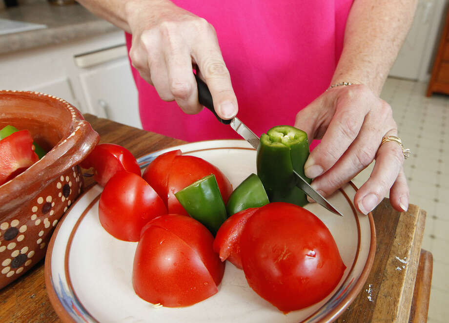 Bunkie Shed slices jalapeño peppers and tomatoes while preparing salsa in her kitchen.