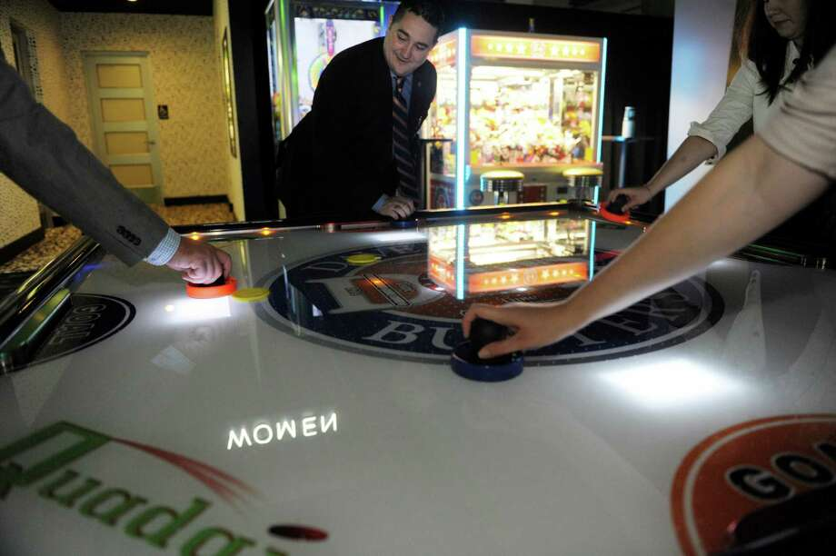 Benjamin Maddy, regional marketing and tourism sales director for Dave and Buster's plays four-person air hockey during a media tour of the new Dave & Buster's, a restaurant/arcade in Crossgates Mall on Thursday, Aug. 22, 2013 in Guilderland, NY.    (Paul Buckowski / Times Union) Photo: Paul Buckowski / 00023601A