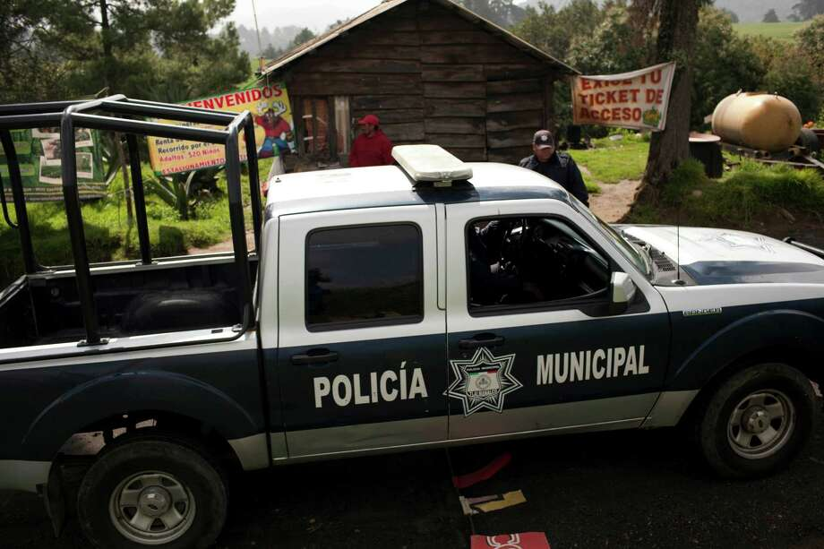 A municipal police truck arrives to the entrance of Rancho la Mesa, which leads to Rancho La Negra in Tlalmanalco, Mexico, Thursday, Aug. 22, 2013. Mexican authorities said Thursday that they have found a mass grave east of Mexico City and are testing to determine if it holds some of the 12 people who vanished from a bar in an upscale area of the capital nearly three months ago. (AP Photo/Ivan Pierre Aguirre) Photo: Ivan Pierre Aguirre, STF / AP
