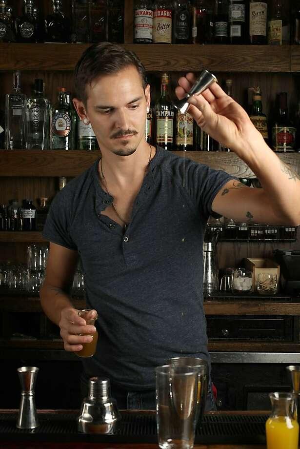 Ramen Shop bartender Chris Lane, who likes a tiki spin on his drinks, makes an Oaxacan Cross. Photo: Liz Hafalia, The Chronicle