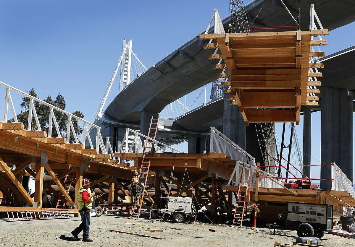 A section of the temporary bike path for the new Bay Bridge is hoisted onto the deck in San Francisco, Calif. on Thursday, Aug. 22, 2013. Caltrans will shut down the Bay Bridge for five days over the Labor Day weekend to connect the new eastern span to the East Bay and Yerba Buena Island and build a temporary bike and pedestrian lane before a permanent one is constructed in about two years.