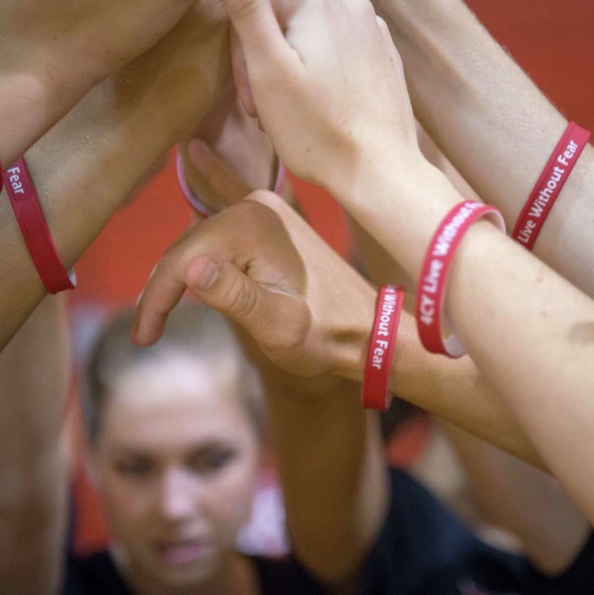 Members of the Memorial High School volleyball team wear bracelets reading