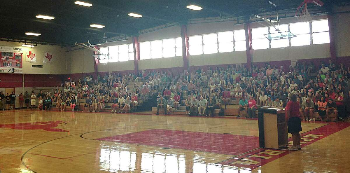 Tina Young addresses a crowd of people from the Memorial HS community in the school's game gym on Monday Aug. 5. Young, a former teacher and coach gave an update on her Stage 4 lung cancer.