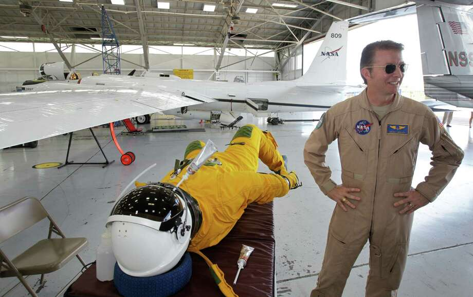 Dean Neeley, a NASA Dryden Research Center research pilot, talks about the pressurized flight suit he wears while flying NASA's ER-2 high altitude aircraft shown during media tour at Ellington Field for NASA's SEAC4RS science flights Thursday, Aug. 22, 2013, in Houston.  SEAC4RS stand for Studies of Emissions and Atmospheric Composition, Clouds and Climate Coupling by Regional Surveys. Three different types of planes carry scientific instruments are used to study how storm systems combine with air pollution from wildfires and other sources to affect our climate. Photo: Melissa Phillip, Houston Chronicle / © 2013  Houston Chronicle