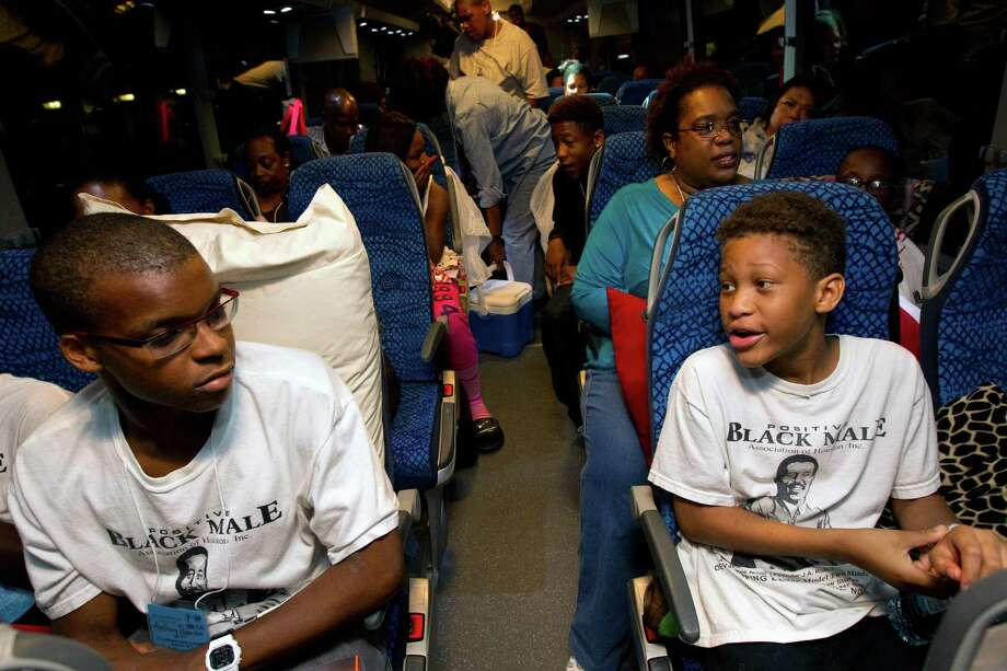 Anthony Roberson, 17, left, looks at Devontae Thompson, 11, right, as they talk on the bus before it departs for Washington D.C., from the Houston Area Urban League, Thursday, Aug. 22, 2013, in Houston.  Students along with supporters boarded the bus to represent Houston in the March To Washington. This year marks a half decade years since Martin Luther King's historic 'I Have a Dream' speech and the march on Washington. Photo: Cody Duty, Houston Chronicle / © 2013 Houston Chronicle