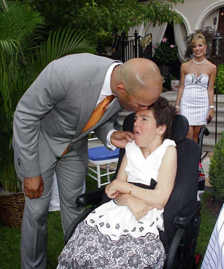 Mariano Rivera plants a kiss on the forehead of Ali Adams Monday night at a fundraising party in Saratoga Springs. Hostess Michele Riggi is in the background. (Photo courtesy George Kalinsky)