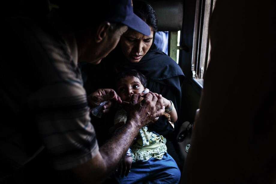 A child receives a polio vaccine inside a railway station in Karachi, Pakistan, a country experiencing a new outbreak. Photo: New York Times
