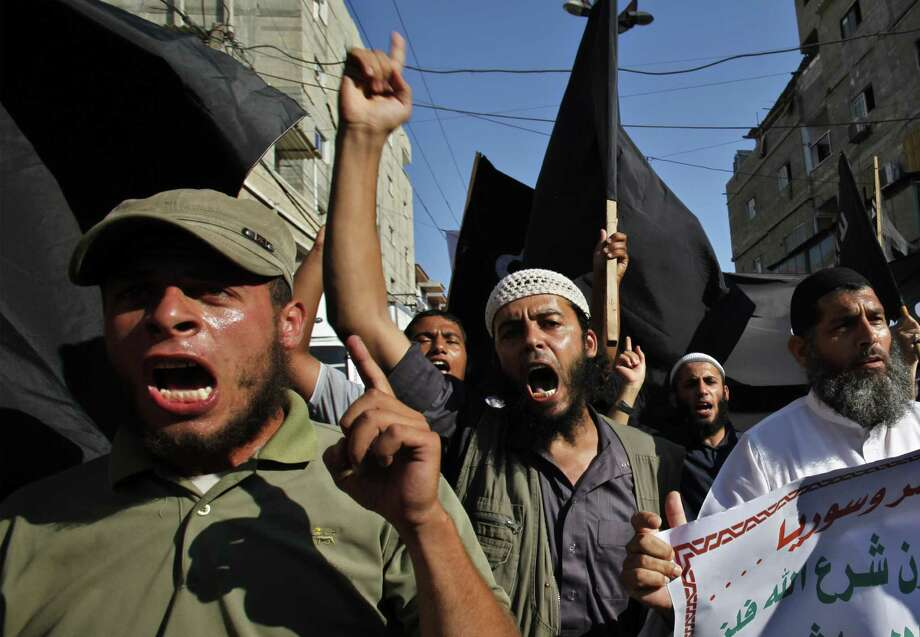 Palestinians in Rafah Refugee Camp in southern Gaza Strip chant slogans while waving black flags during a protest against the Egyptian and Syrian regimes. Photo: Adel Hana / Associated Press