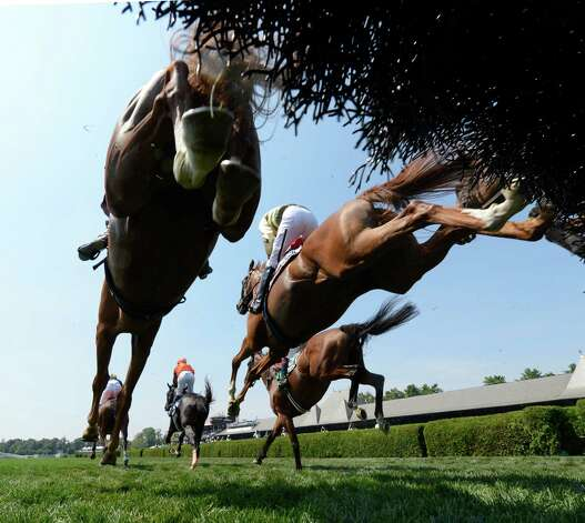 The field cascades over one of the fences during the running of The 72nd running of The New York Turf Writers Cup Thursday afternoon, Aug. 22, 2013, at Saratoga Race Course in Saratoga Springs, N.Y. Italian Wedding with jockey Bernard Dalton, center, was the eventual winner of Thursday's featured race.  (Skip Dickstein/Times Union) Photo: SKIP DICKSTEIN