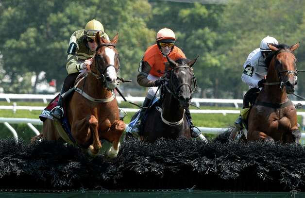 Italian Wedding with jockey Bernard Dalton, in the saddle, left,  flies over the final fence and runs on to win The 72nd running of The New York Turf Writers Cup Thursday afternoon, Aug. 22, 2013, at Saratoga Race Course in Saratoga Springs, N.Y.  (Skip Dickstein/Times Union) Photo: SKIP DICKSTEIN