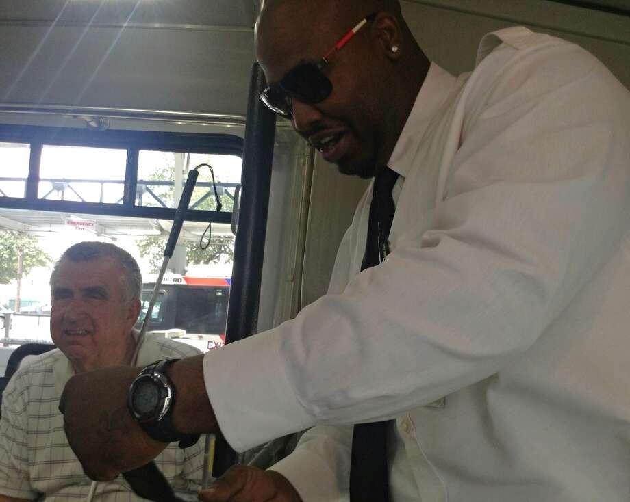 MetroLift driver Santana Barns, right, checks Joe Schaidnagle's ID before leaving downtown on Aug. 22, 2013. Schaidnagle is blind.