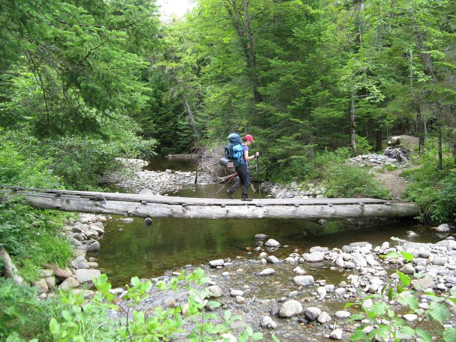 Photo by Herb Terns. Gillian Scott crosses a log bridge near Miller's Falls along the Northville-Placid Trail.