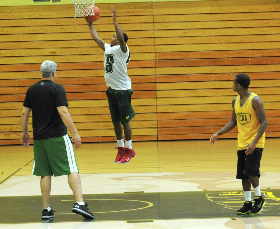 Marquis Wright goes up for a basket while coach Jimmy Patsos, left, and Evan Hymes watch as the Siena men's basketball team practices in preparation for a trip to Montreal Tuesday, Aug. 20, 2013 in Loudonville, N.Y. They will be playing a series of games against Canadian teams. (Lori Van Buren / Times Union) Photo: Lori Van Buren / 00023580A