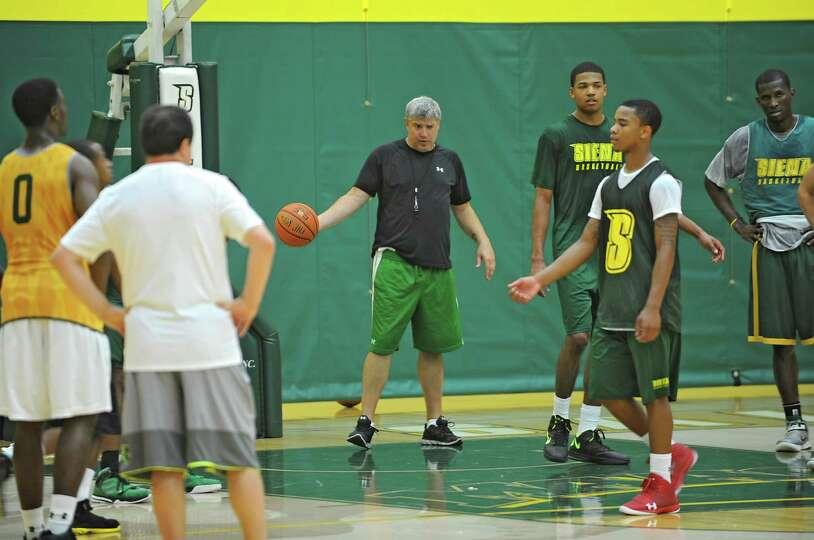 Head coach Jimmy Patsos, center, talks to his players as the Siena men's basketball team practices i
