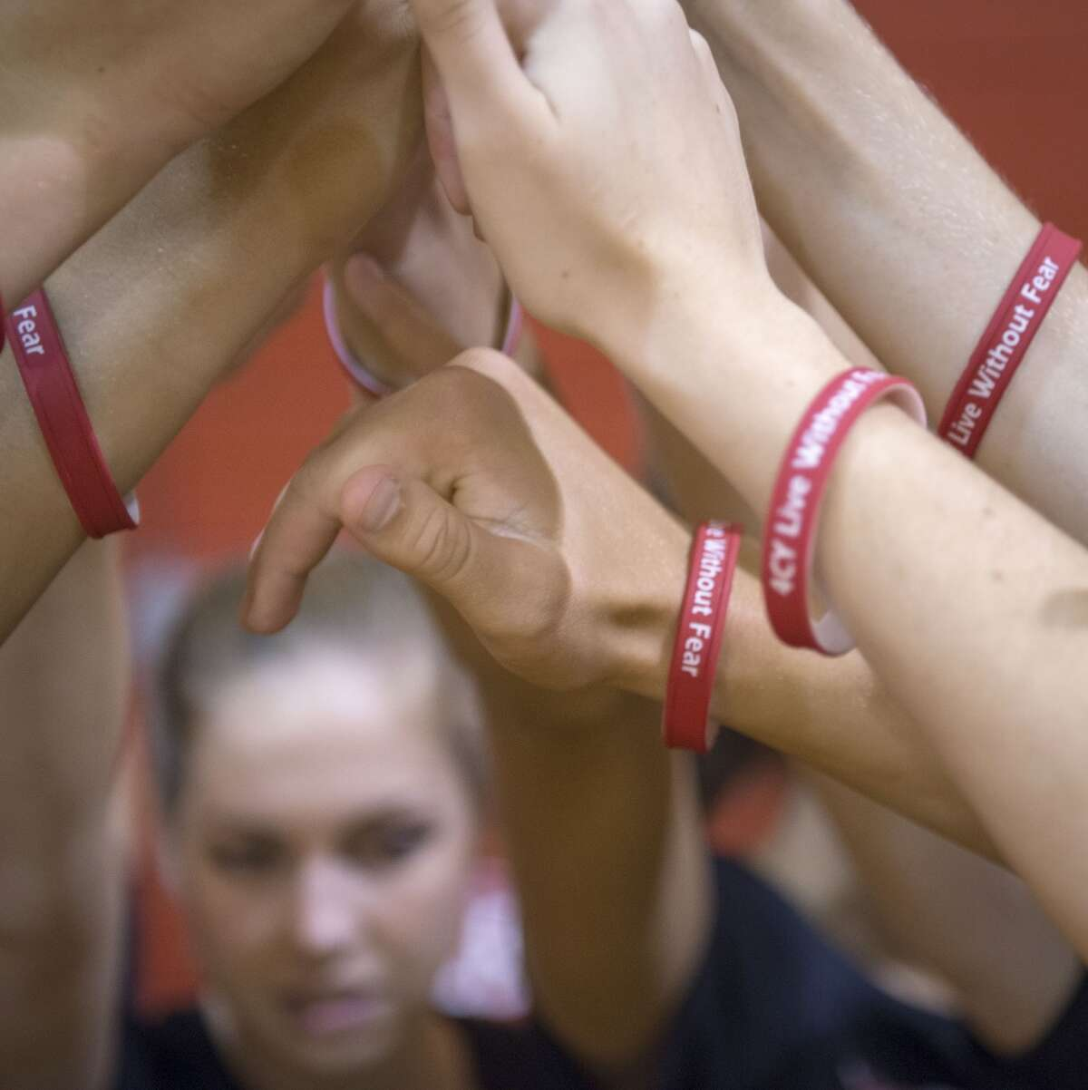 Members of the Memorial volleyball team wear bracelets reading