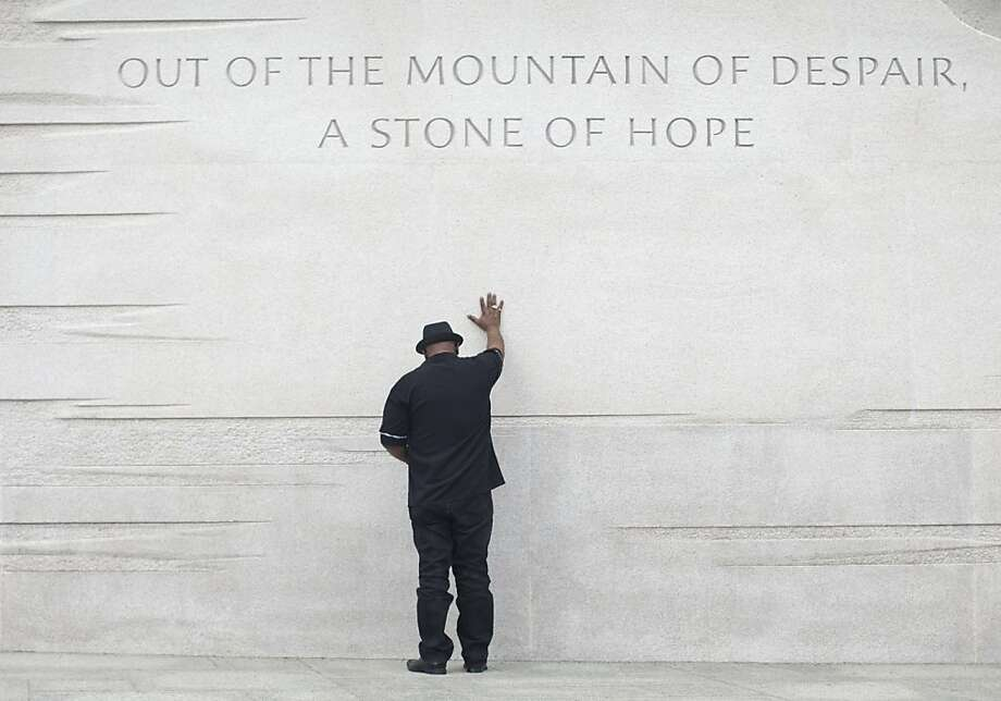 Rev. Bobby Turner or Columbus, Ohio, places his hand on the Martin Luther King Jr. Memorial, Thursday, Aug. 22, 2013, in Washington. President Barack Obama is scheduled to speak at a ceremony on the 50th anniversary of the 1963 March on Washington. (AP Photo/Carolyn Kaster) Photo: Carolyn Kaster, Associated Press