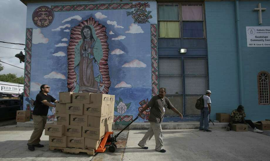 Volunteers Kent Nabarrete and William Santos move a pallet of boxes as volunteers distribute food to families in need. Photo: Helen L. Montoya, San Antonio Express-News