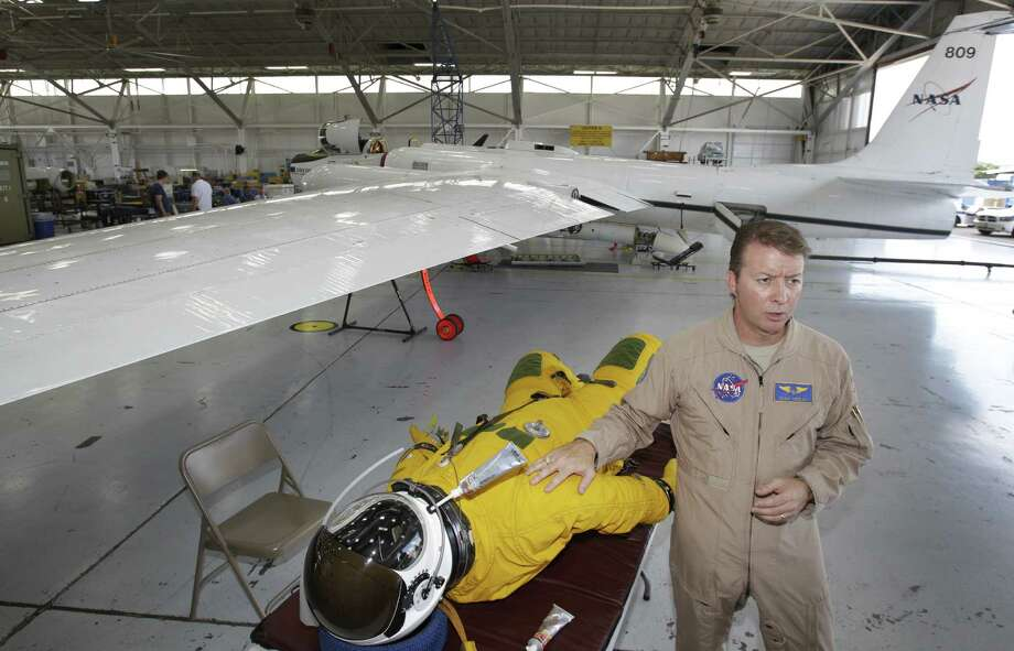 NASA pilot Dean Neeley talks about the pressurized flight suit he wears while flying high-altitude aircraft, which is being used to study air pollution. Photo: Melissa Phillip / Houston Chronicle
