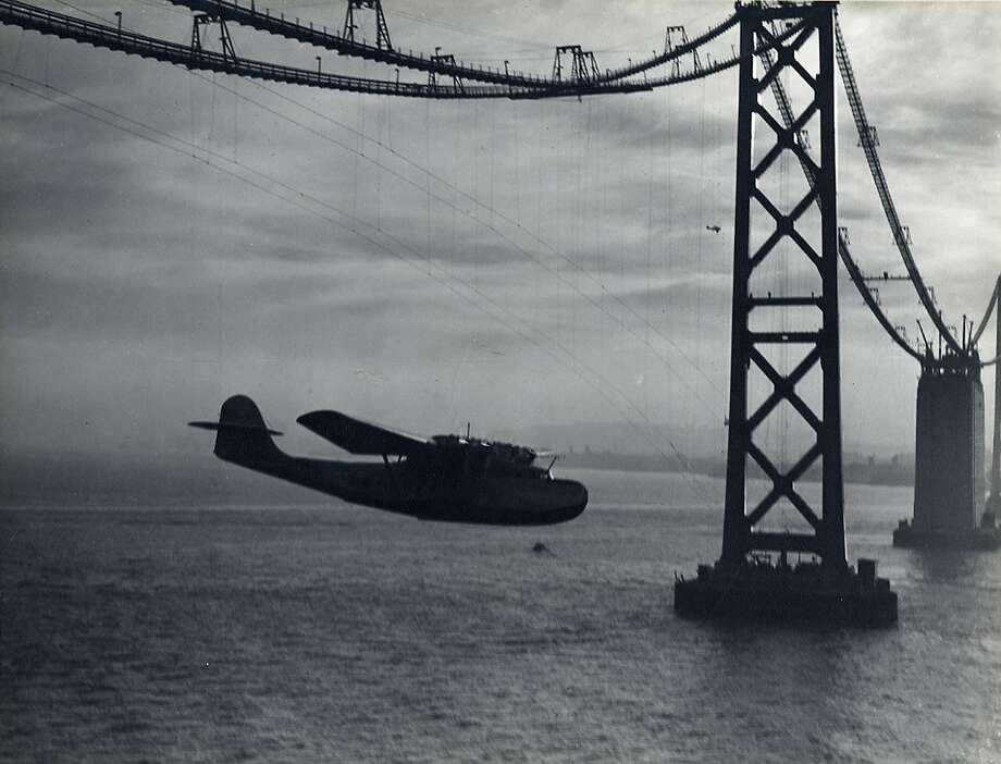 Fully loaded with fuel, over 110,000 pieces of airmail, and its seven-man crew, the China Clipper struggled to clear the Bay Bridge on its inaugural transpacific flight on Nov. 22, 1935. At the last moment Capt. Edwin C. Musick, veered under the bridge cable and threaded through the tension wires. By the time they reached the Golden Gate Bridge, also under construction, the China Clipper had gained enough altitude to clear the south tower. Photo: Clyde Sunderland, SF Airport Museums