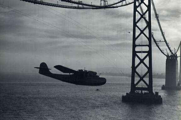 Fully loaded with fuel, over 110,000 pieces of airmail, and it's seven-man crew, the Pan American Airways Martin M-130 christened China Clipper struggled to clear the yet completed San Francisco-Oakland Bay Bridge on it inaugural transpacifc flight of November 22, 1935. At the last moment Capt. Edwin C. Musick, Pan American's Chief Pilot No. 1 and a Master of Ocean Flying Boats,  veered under the bridge cable and threaded through the tension wires. By the time they reached the Golden Gate Bridge, also under construction, the China Clipper had gained enough altitude to clear the south tower.  Photograph by Clyde Sunderland San Francisco Airport Museums, gift of Thomas Northrop   Ran on: 11-03-2005 Early for the party  for the China Clipper at SFO's aviation museum are (from left) Bjorg Trucco, Ross Butler, Ululani Jung and Annie Husack.Ran on: 03-21-2006 In 1936, the first cars drive across a brand-new Bay Bridge. The upper deck is designated for two-way traffic, the lower deck reserved for trains. This photo was taken from the top of a tower.Ran on: 03-21-2006 In 1936, the first cars drive across a brand-new Bay Bridge. The upper deck is designated for two-way traffic, the lower deck reserved for trains. This photo was taken from the top of a tower.