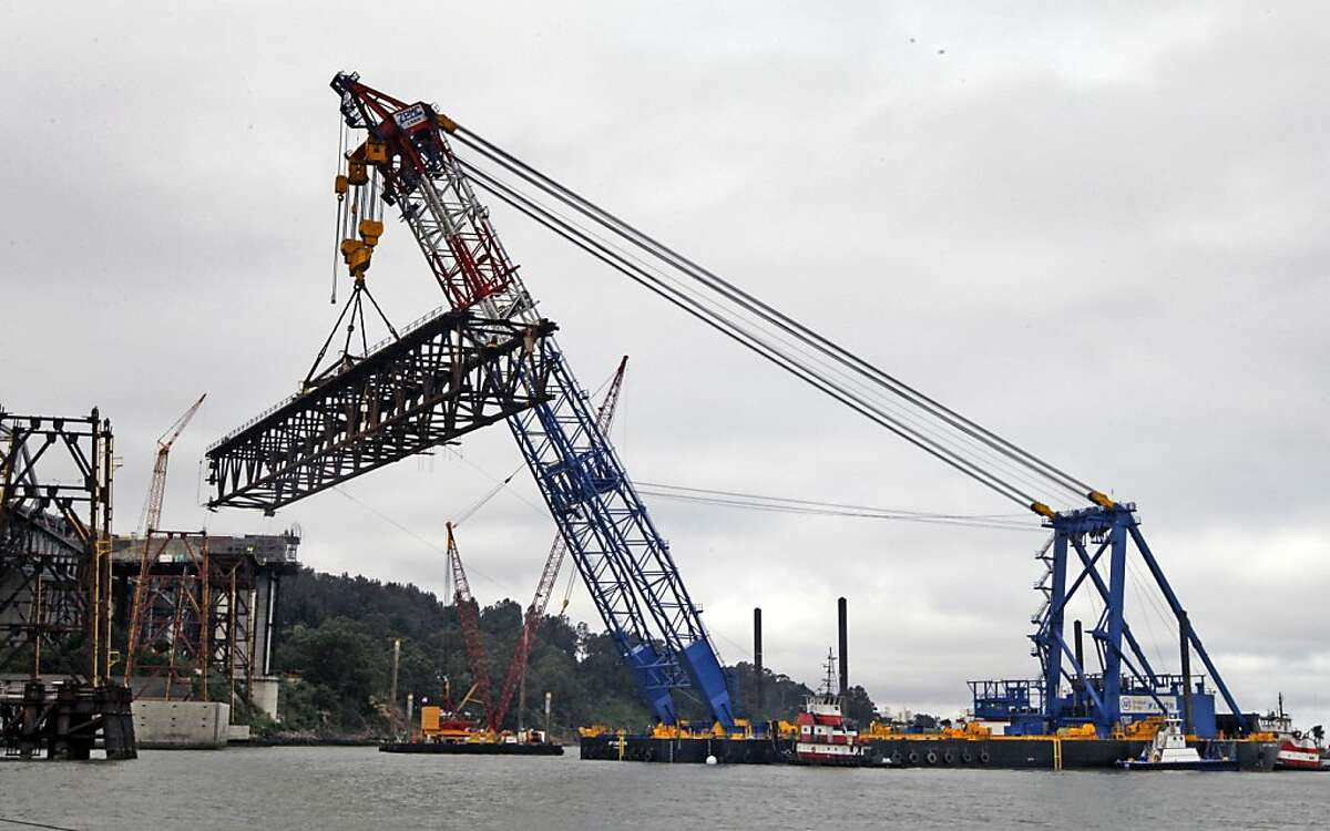 A massive shear leg crane mounted on a barge went into use lifting a all steel trust that weights almost 12,000 tons. Friday, May 29, 2009. The trust will carry vehicles temporarily over the San Francisco-Oakland Bay Bridge for next next few years as work continues on the new Skyway portion that will eventuly connect with Yerba Buena Island. The barge measures 400 by 100 feet and was custom built in Portland Or but was outfitted with the massive six story high carne dubbed the Left Coast Lifter in Shanghai China,