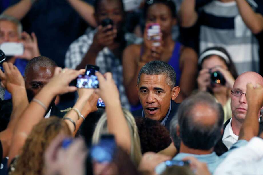 President Barack Obama is greeted as he arrives at the University at Buffalo, Thursday, Aug. 22, 2013, in Buffalo, N.Y., where he began his two day bus tour to speak about college financial aid. (AP Photo/Keith Srakocic) ORG XMIT: NYKS105 Photo: Keith Srakocic / AP