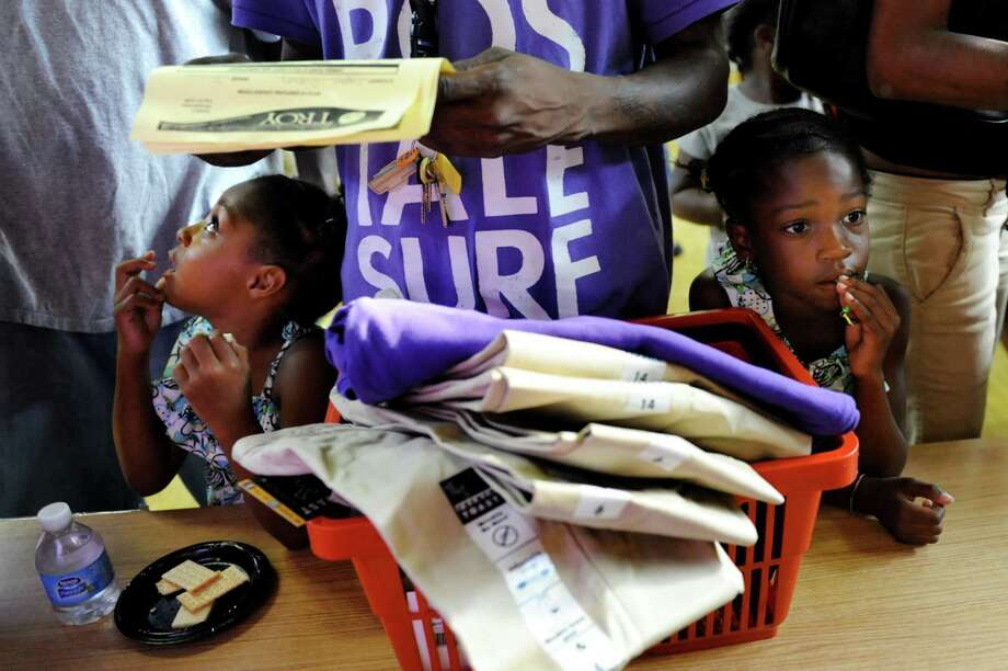 Nevaeh Dickson, 5, left, and her sister Kayjohna Dickson, 7, wait as their father, John, collects their uniforms on Thursday, Aug. 22, 2013, at School 2 in Troy, N.Y. (Cindy Schultz / Times Union) Photo: Cindy Schultz / 00023546A