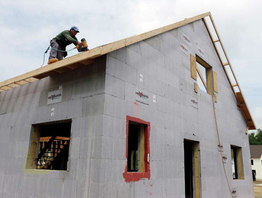FILE - In this July 9, 2013, file photo, a  construction worker drills on the  roof of a new home  in New Paltz, N.Y.  The Commerce Department reports on new-home sales for July, on Friday, Aug. 23, 2013. Photo: Mike Groll