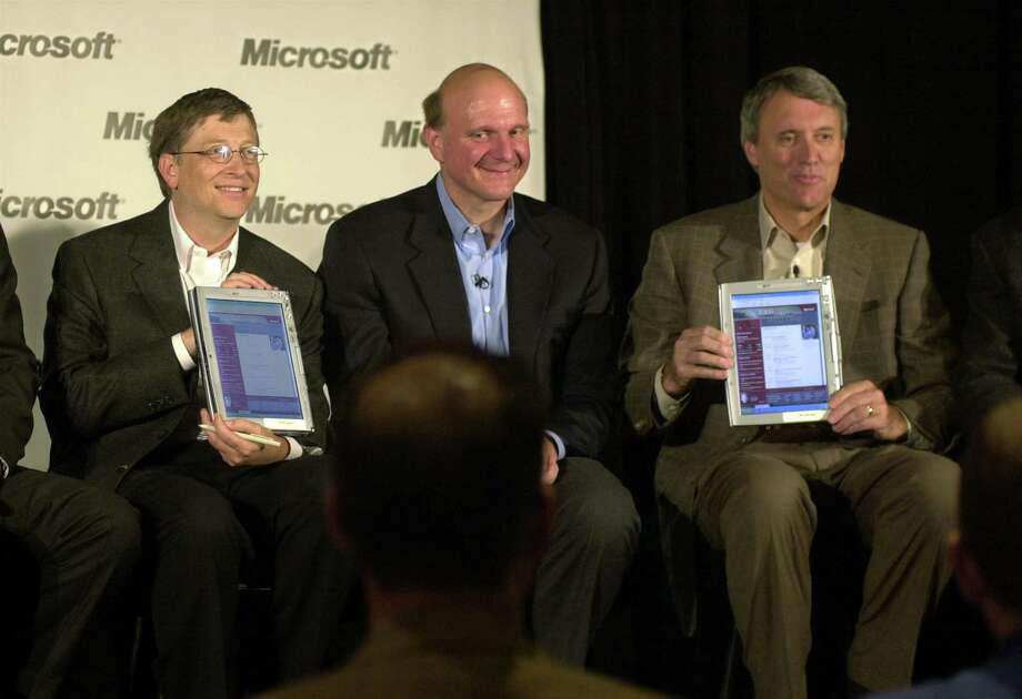 Balmer sits between Gates and Toys 'R' Us Chairman and CEO John Eyler, who hold up Windows XP Tablet PCs during the Microsoft CEO Summit on May 22, 2002 in Redmond, Wash. Photo: Ron Wurzer, Getty Images / Getty Images North America