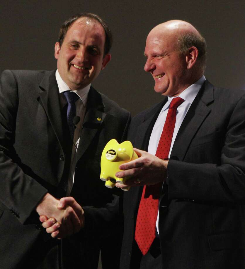 Ballmer accepts a yellow piggy bank from German electricity provider Yello Strom head Martin Vesper at a press conference at the CeBIT technology fair a day before the fair's official opening on March 3, 2008 in Hanover, Germany. Photo: Sean Gallup, Getty Images / 2008 Getty Images