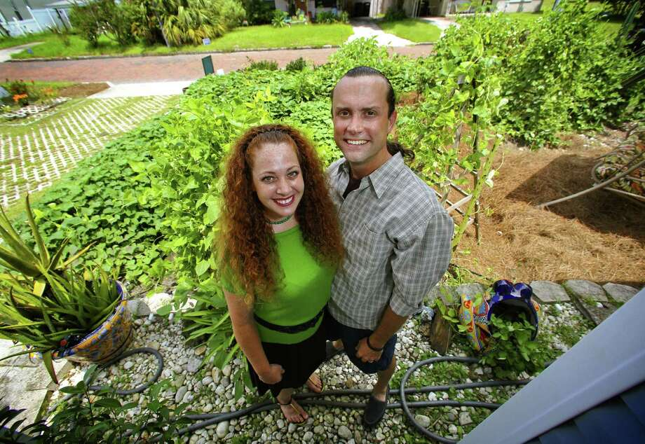 Jason and Jennifer Helvenston stand among the sweet potato vines in their front-yard garden in Orlando, Fla. Photo: Joe Burbank, MBR / Orlando Sentinel