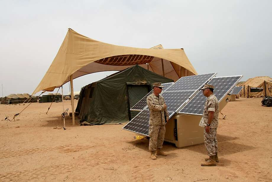 "CAPTION: ""Maj. Sean M. Sadlier (left) of the U.S. Marine Corps Expeditionary Energy Office explains the solar power element of the Expeditionary Forward Operating Base concept to Col. Anthony Fernandez during the testing phase of this sustainable energy initiative here, May 19. The ExFOB is designed primarily for use by small Marine Corps units at forward operating bases in Afghanistan. Fernandez, a Marine Corps Reservist with a combined 28 years in the Corps, is the African Lion 2010 task force commander here."" DATE: May 21, 2010 BY: U.S. Marine Forces Africa LOCATION: The African Lion operation, where this comes from, was based in Morocco Photo: Insight25_breen_PHa, Maj. Paul Greenberg"