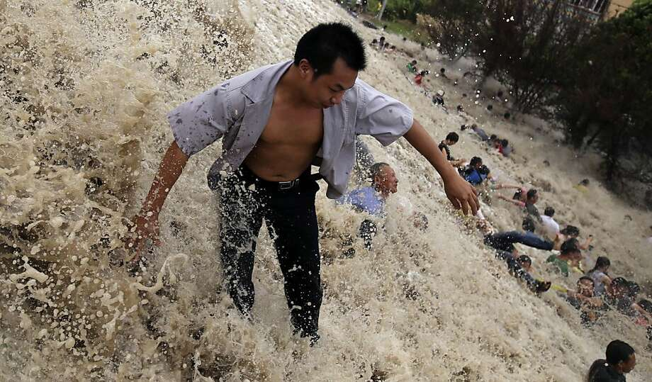 """Tidal wave strikes:A large wave washes spectators down a slope during an unusually high """"Haining tide"""" - a   daily phenomenon in Haining, China, caused by the river tide crashing against its banks.   The tide was especially strong because Typhoon Trami, China's 12th typhoon of the   season, made landfall in Fujian Province hours before. Photo: Stringer, AFP/Getty Images"""